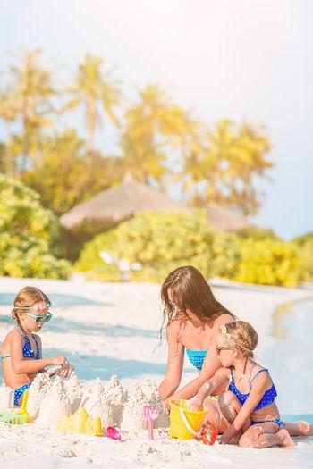 Siblings sitting on shore against water