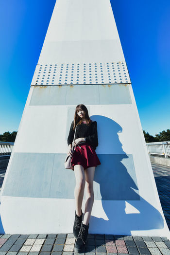 Full length portrait of young woman against blue sky