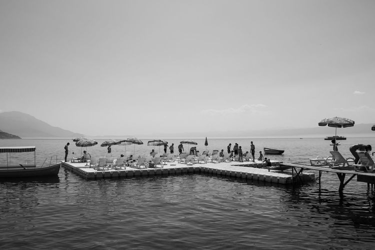 sunbathing at lake Ohrid Beach Beauty In Nature Blackandwhite Clear Sky Day Island Lake Lake View Large Group Of People Monochrome Mountain Nature Nautical Vessel Outdoors People Real People Scenics Sea Sea And Sky Sky Sunbathing Tranquility Transportation Water Waterfront
