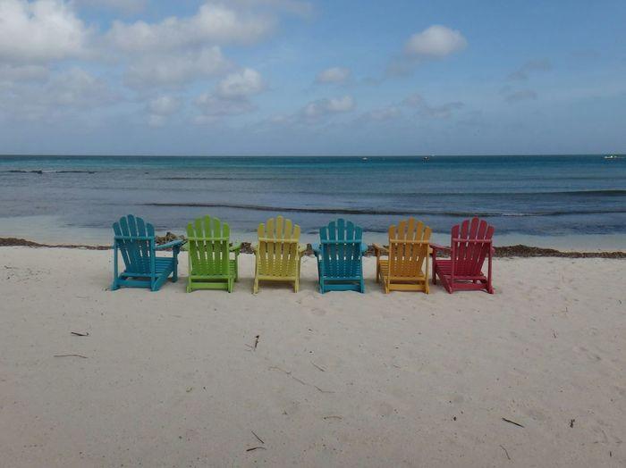 Adirondack chairs on shore at beach