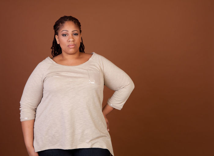 Portrait Of Overweight Woman Standing Against Brown Background
