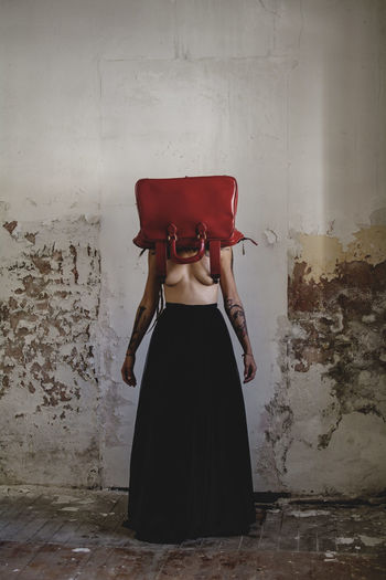 Shirtless Woman Wearing Bag While Standing Against Wall
