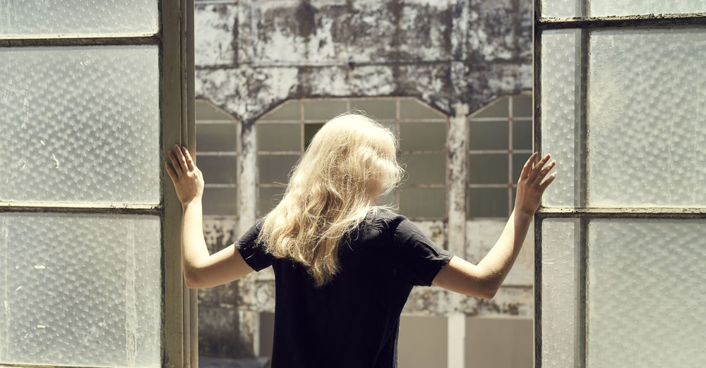 Rear view of woman standing in front of window