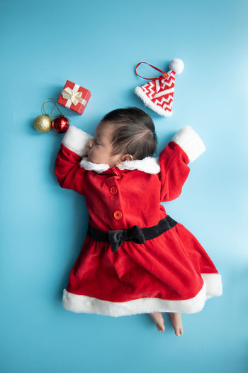 Directly above shot of baby girl wearing santa claus costume sleeping on blue background