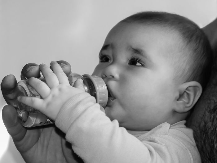 Close-up of cute baby girl drinking milk at home