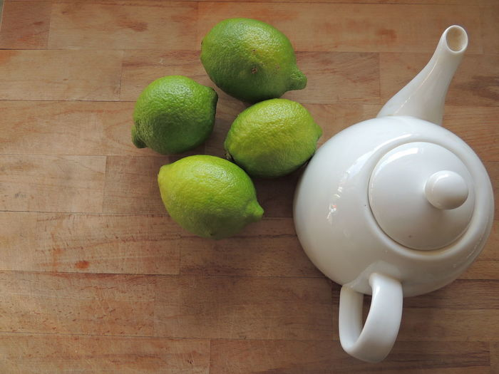 High angle view of limes by teapot on wooden table