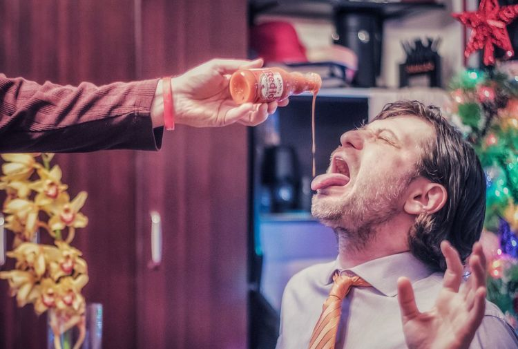Cropped Hand Pouring Sauce On Man Tongue