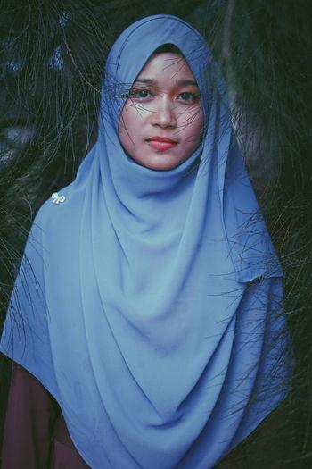 Portrait of woman wearing hijab by branch