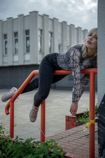 Portrait of young woman lying on railing