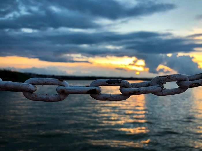 Sunset over a metal chain near a lake