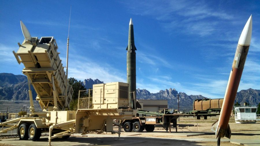 Rocket launcher and missiles at military base against sky