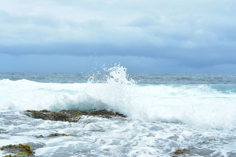 Scenic View Of Splashing Sea Waves Against Cloudy Sky
