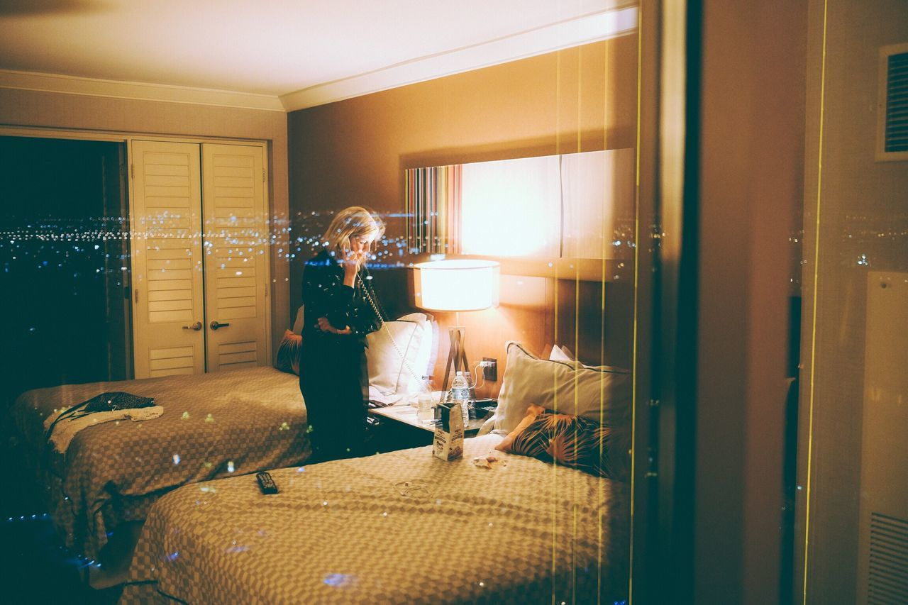 Reflection Of Woman Talking On Landline Phone In Hotel Room