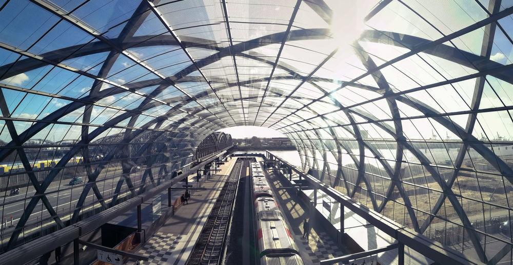 Railroad tracks in modern tunnel against sky