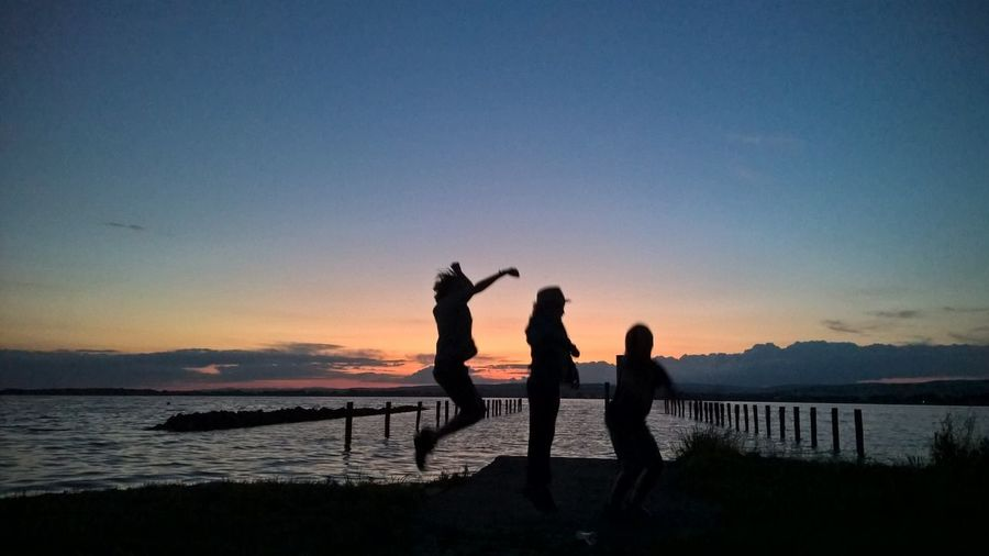 Silhouette Siblings Enjoying On Lakeshore Against Sky During Sunset