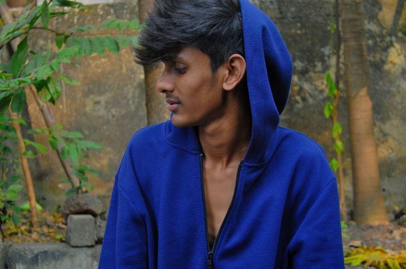 Young man wearing hooded shirt looking away