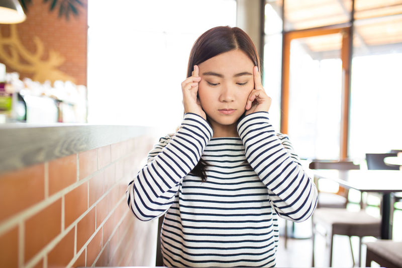 Young woman suffering from headache while sitting in restaurant