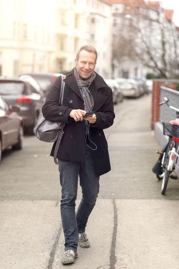 Smiling Man Listening Music Through Headphones While Walking On Footpath