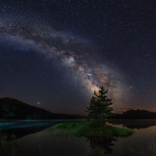 Night landscape with colorful Milky Way and light at mountains. Starry sky with hills at summer. Beautiful Universe. Lake in front. Space background, shot from Bulgaria Lake Water Sky Astronomy Night Reflection Galaxy Milky Way Idyllic Space Nature Way Milky Universe Astrophotography Dark Mountain Landscape Tree Reflection Cosmos Flower