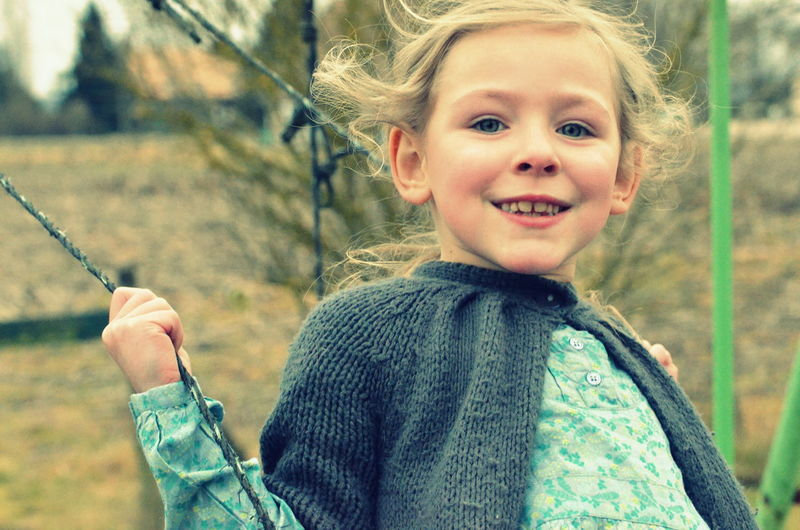 Portrait of girl sitting in swing
