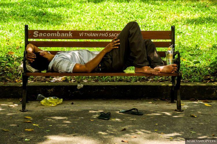 Título: Buenos días Saigón/Good morning Saigon. Autor: Marcus Populus Lugar: Saigón, Vietnam. Cámara: SONY SLT A65V Punto F: f/5.6 Tiempo de exposición: 1/160s Velocidad ISO: 400 Distancia focal: 100mm Men One Person Park Park Bench Relaxation Sleeping Social Issues Tired