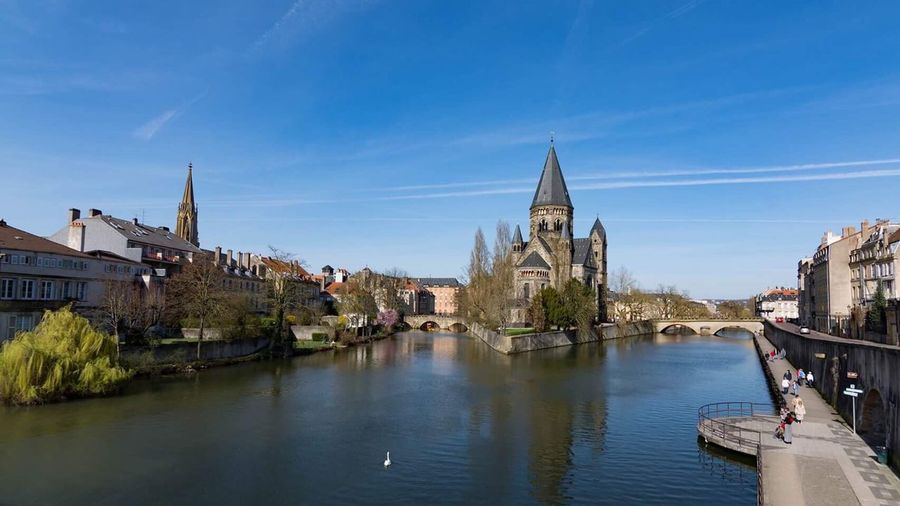 Church By River In City Against Blue Sky