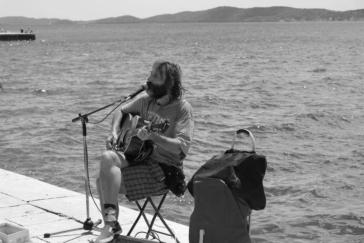 Man sitting at sea shore