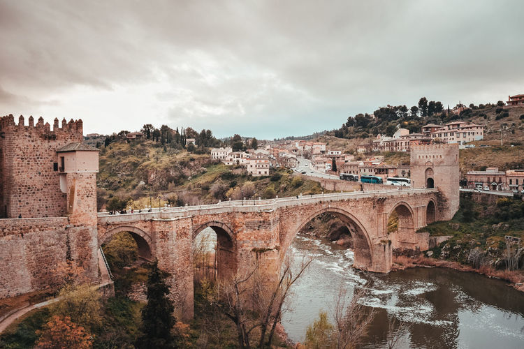 Old arched bridge crossing a river in toledo city.