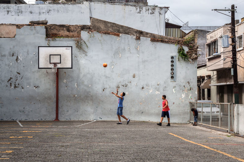 Full length of friends playing basketball against buildings