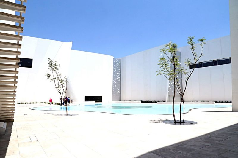 Museum time. Building Exterior Architecture Tree Built Structure Sunlight Growth Swimming Pool Outdoors Shadow Clear Sky Day Real People Blue Sky One Person Whitewashed Nature People Museo Internacional Del Barroco Puebla De Los Angeles Puebla MX Mexico Modern Architecture Art Is Everywhere Break The Mold