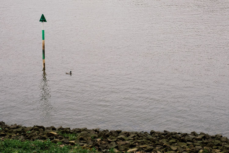 High angle view of pole by lake against wall