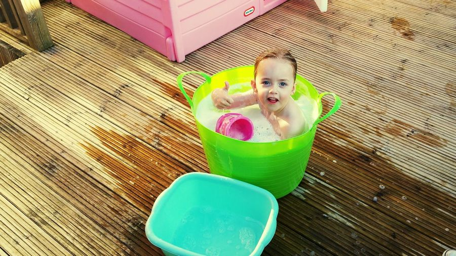 High Angle Portrait Of Smiling Girl In Bucket Full Of Water