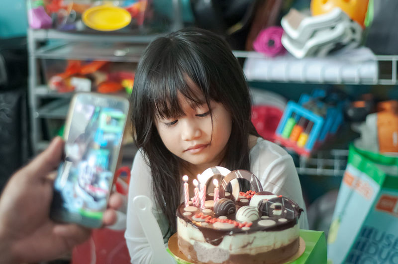 Close-up of cute girl sitting by cake at home