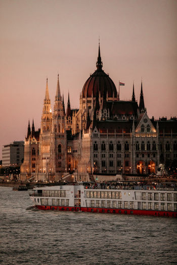 Hungarian parliament building by river against clear sky at sunset