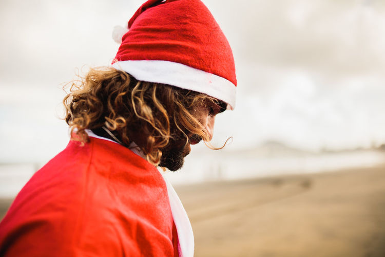 Side view of man wearing santa costume at beach