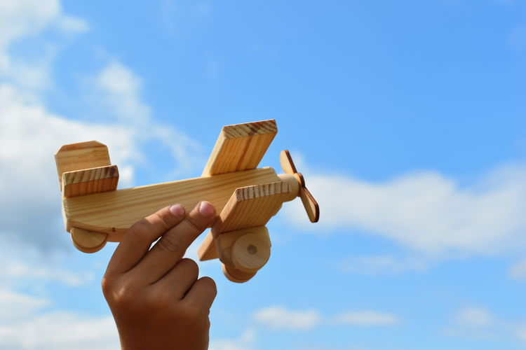 Low angle view of person holding model airplane against sky