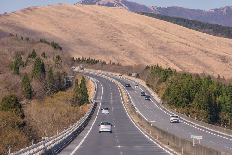 Road Transportation Land Vehicle Car Mode Of Transportation The Way Forward Motor Vehicle Symbol Highway Road Marking Direction Marking Sign Motion Tree Mountain on the move High Angle View Plant Nature No People Multiple Lane Highway Diminishing Perspective Outdoors Dividing Line