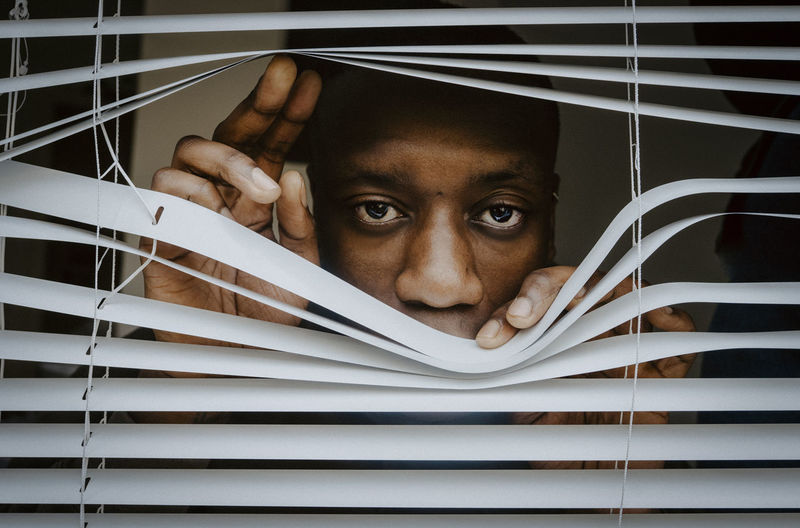 Portrait of young man hiding behind window