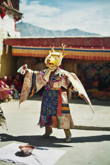 Performer In Costume Dancing Outside Temple During Festival