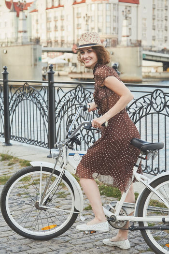 Portrait of young woman with bicycle standing by canal