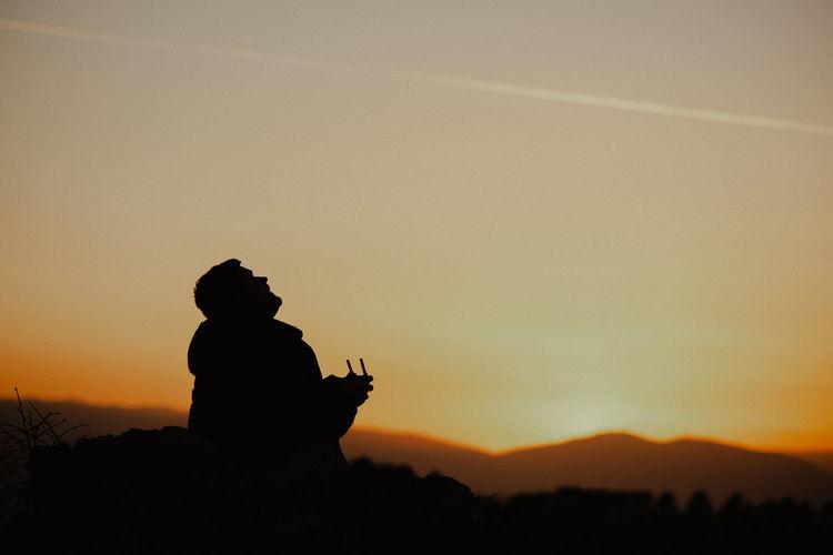 Silhouette man sitting against orange sky
