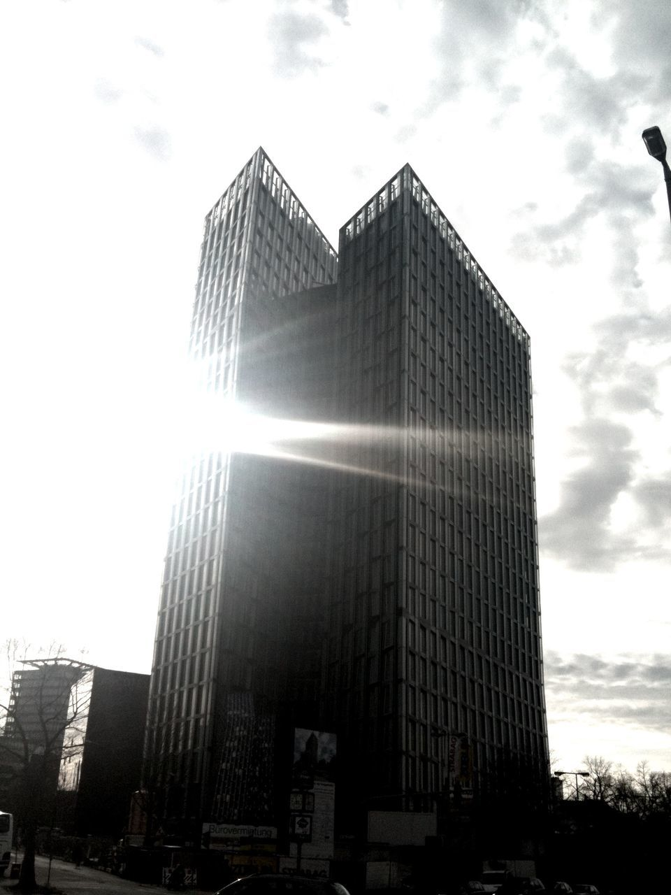 architecture, built structure, low angle view, sky, building exterior, skyscraper, day, sunlight, cloud - sky, outdoors, sun, modern, no people, city