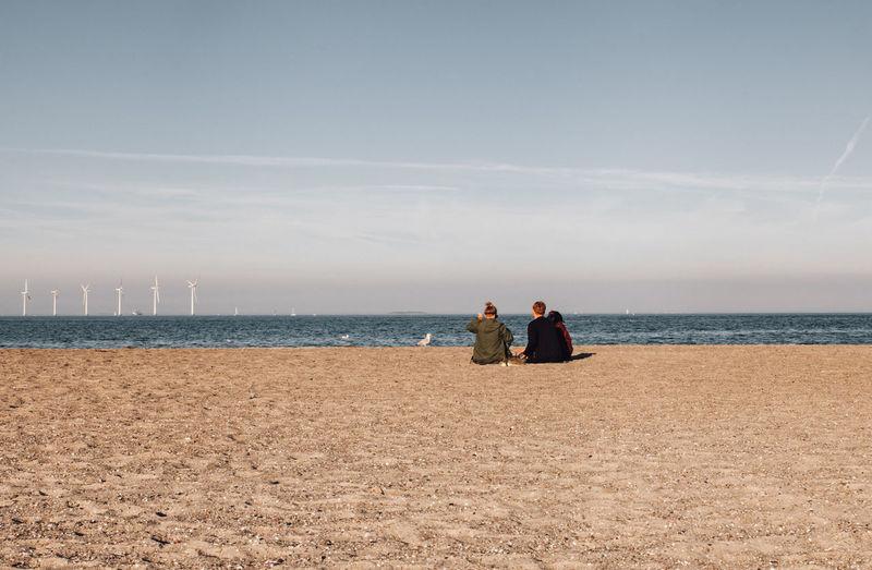 Men on beach against sky