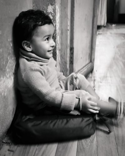 Side view of cute boy sitting on floor at home