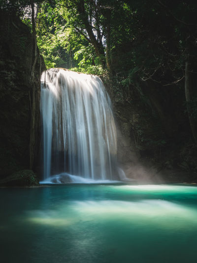 Scenic waterfall smooth stream, sunbeam and turquoise pond. erawan falls, kanchanaburi, thailand.