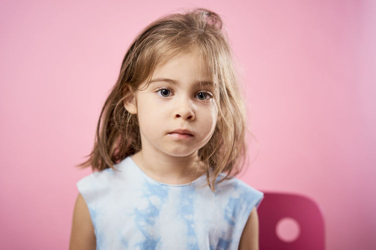 Portrait Childhood Indoors  Pink Background Looking At Camera Studio Shot Colored Background Headshot Child Hair Front View One Person Blond Hair Pink Color Cute Innocence Females Hairstyle Women Making A Face Human Face