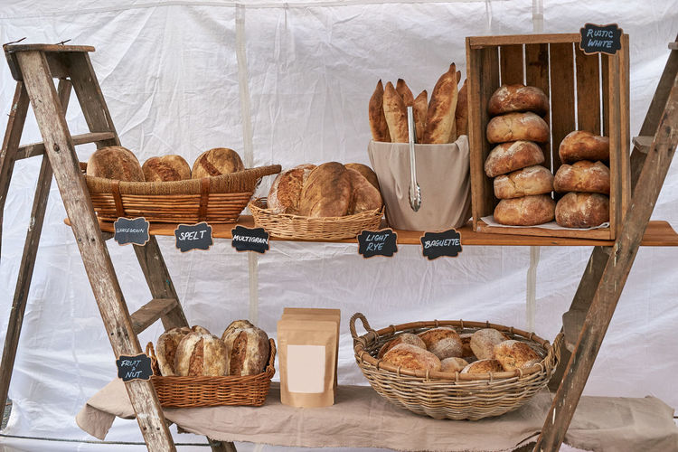 The simple, rustic and practical bread display of a local baker; taken at the Yamba farmer's market in 2019. Fresh loaves arranged in baskets, on a simple trestle of boards and ladders. Bread Basket Food Freshness Wicker Baked Retail Display Wood - Material Brown Ready-to-eat Bakery Bun Still Life Display Fresh Bread Fresh Baked Organic Farmer's Market Bread Stall Market Stall Baked Goods Breads Loaves Loaf Sourdough