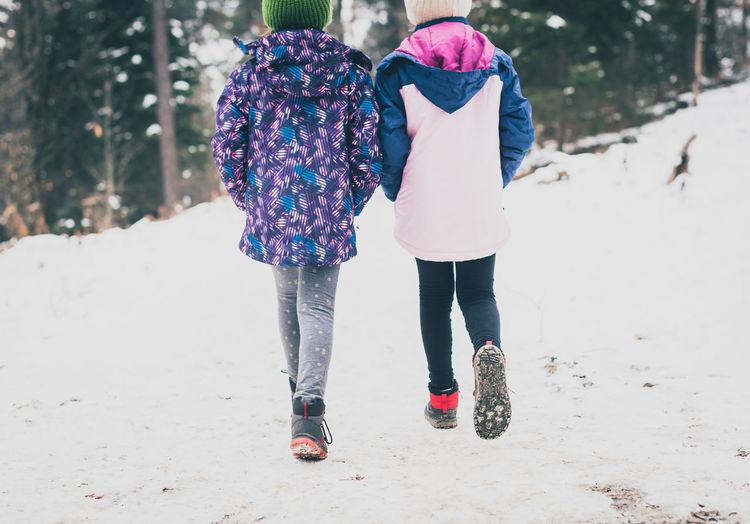 Rear view of women walking on snowy field
