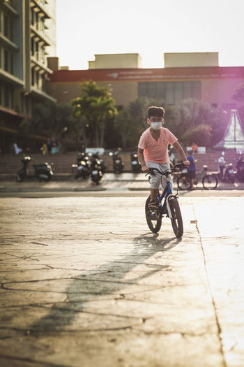Kid riding bicycle on street in city, against the sunlight