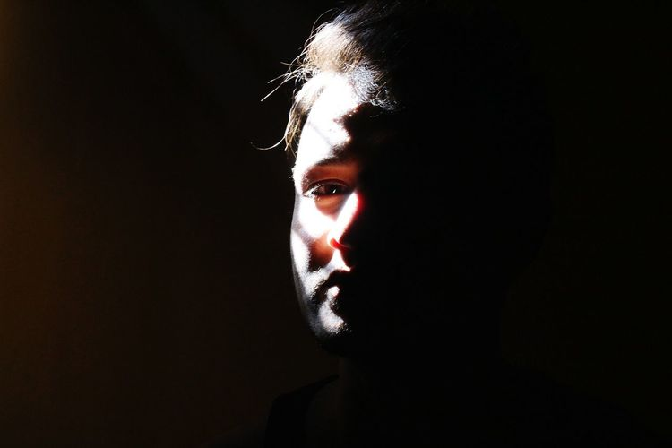 Sunlight falling on man face in darkroom